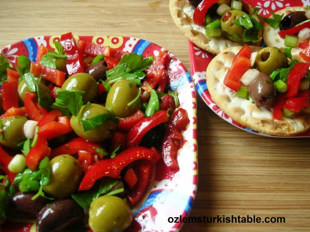 Olives salad with red peppers, spring onions and pomegranate molasses; summer on a plate