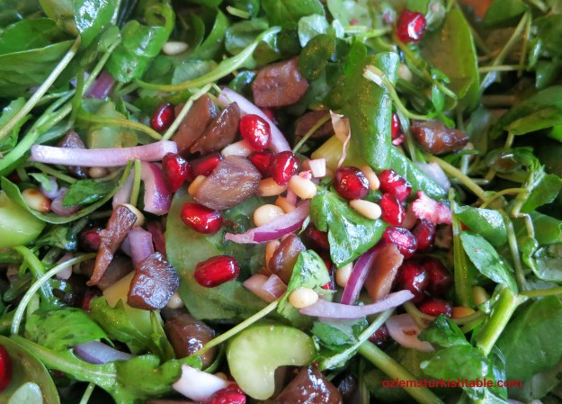 Refreshing spinach salad with celery, red onion, pomegranate seeds and sauteed nuts.
