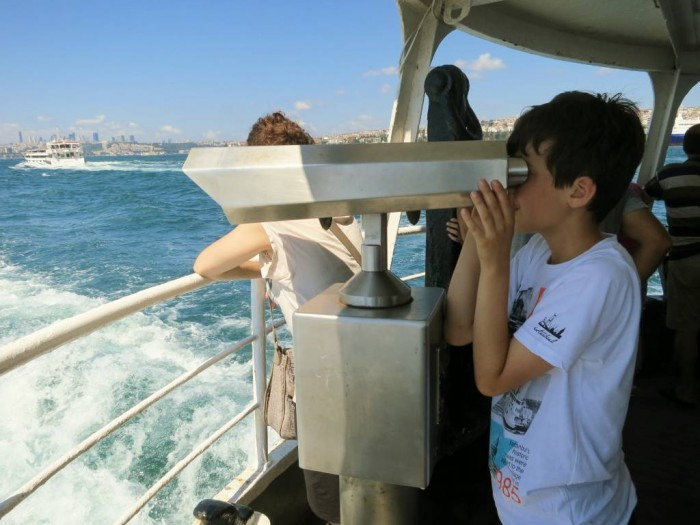My son trying the telescope at the ferry