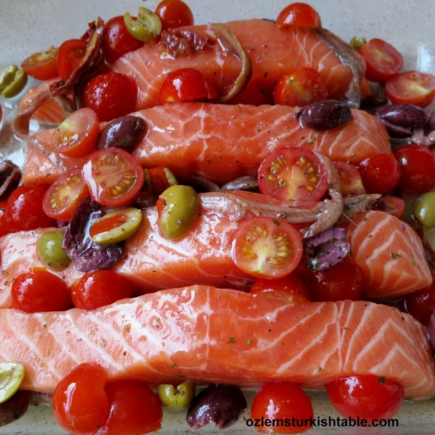 Spread the cherry tomatoes, olives and the anchovy fillets over and around the salmon fillets.