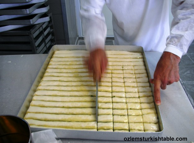 The Usta, master cuts the sheets first horizontally and poured melted butter over them